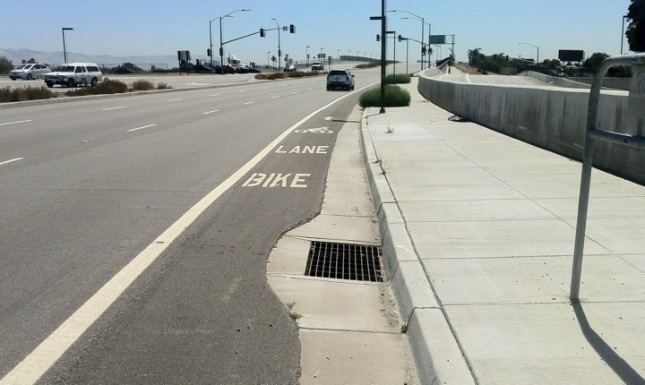 The grates further down road are safer. Why did they use an old style one?