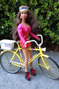 Asha rides a 70's ten-speed in a Soul Train jumpsuit and kente cloth hat.