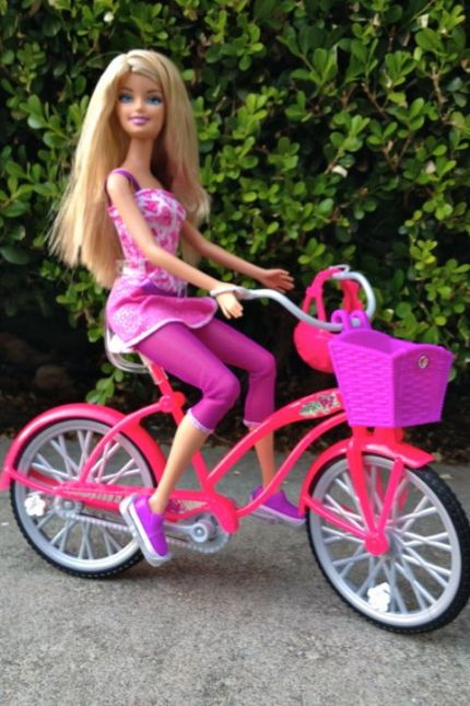 Barbie rides a pink beach cruiser in a knit dress and capri leggings.