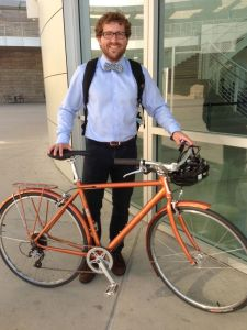 Bow tie, horn-rim glasses and dress shirt on a burnt orange city bike.