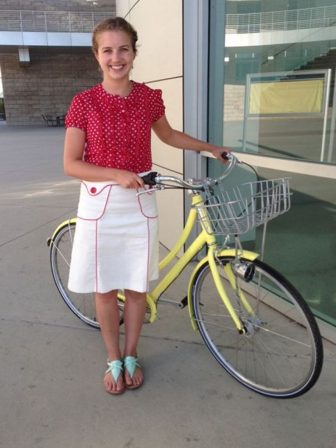 Red polka dots and retro piped skirt on a sunny yellow loop frame.