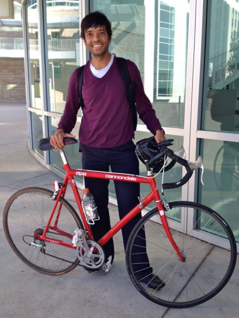 V-neck sweater and cycling shoes on a early-1990s aluminum road bike.