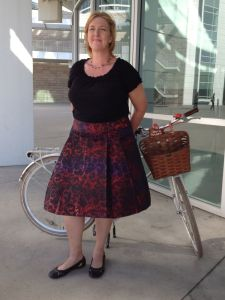 Ballet neck top and ballet flats with a full pleated skirt on a wicker basket mixte.