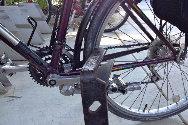This bracket SHOULD slip around the chain stays and between the spokes.