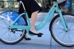 Rubber soled ballet flats are perfect for bike's flat pedals and for her 10 minute walk to the bike share station.