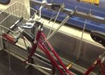 Caltrain bungees work as a makeshift bike stand. Otherwise, you can carefully lay the bike down drive train side up.